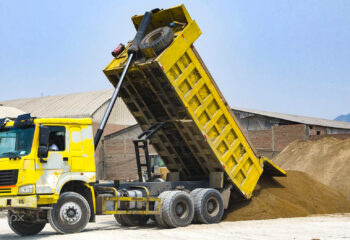 yellow dump truck delivering a load of dirt for a project at a construction site