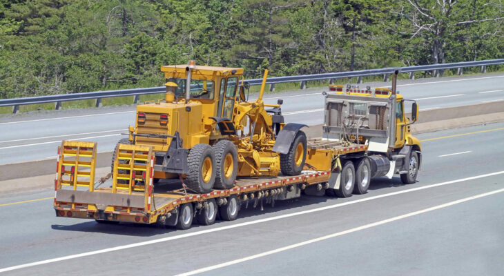 elevated rear quarter view of a flatbed semi truck on a highway transporting a road grader