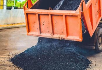orange dump truck unloads fresh asphalt into the spreader on a road in the city
