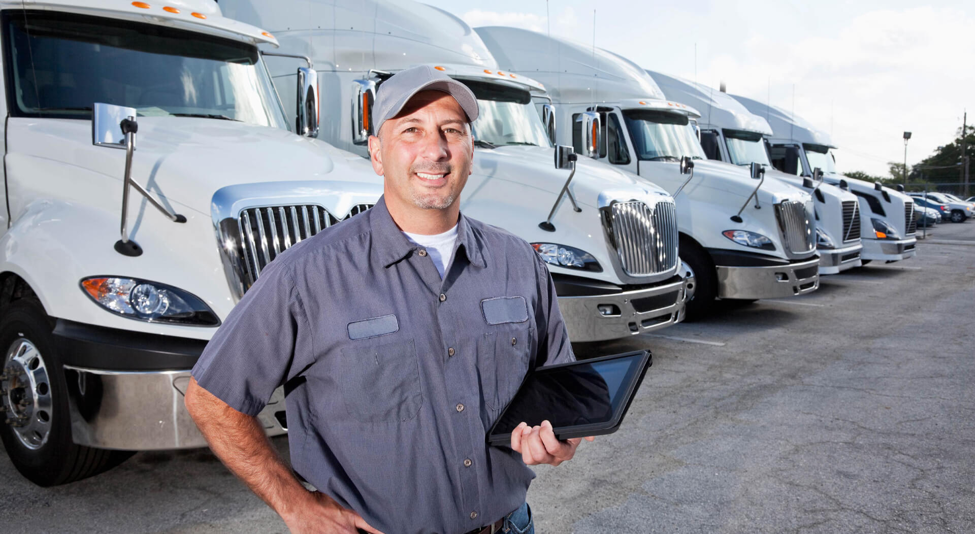 a truck owner is holding a tablet with his left hand while standing in a large parking lot in front of several large trucks