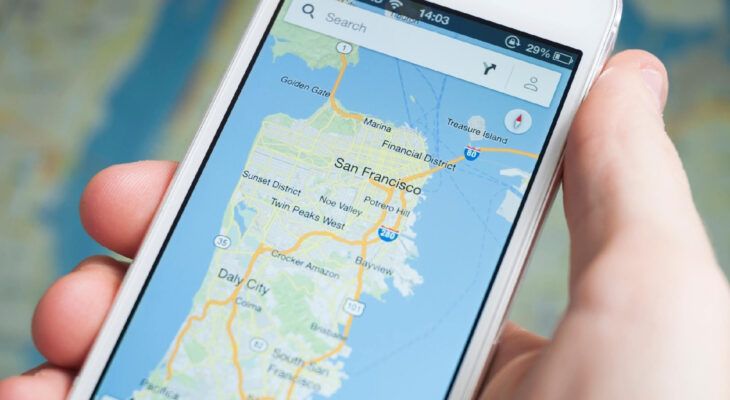 person holding an iphone 5 with google maps open