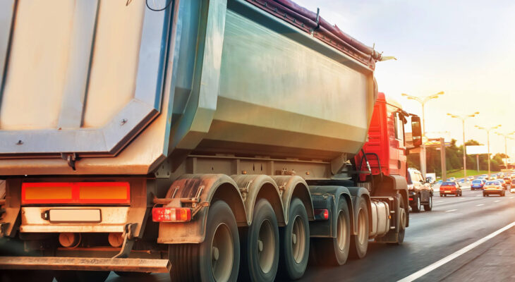 dump truck goes at dusk on highway