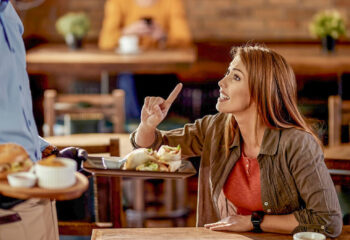 young woman arguing with waiter who is serving her food