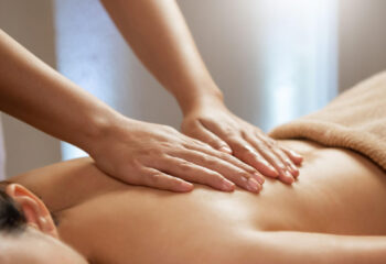 masseuse doing massage on a female body in the spa salon