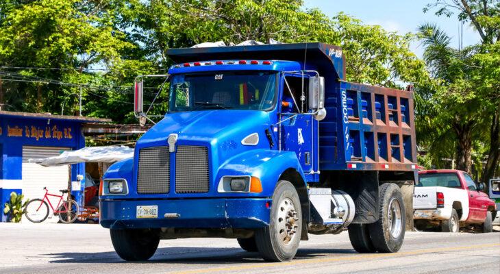 blue Kenworth T300 dump truck in the town street