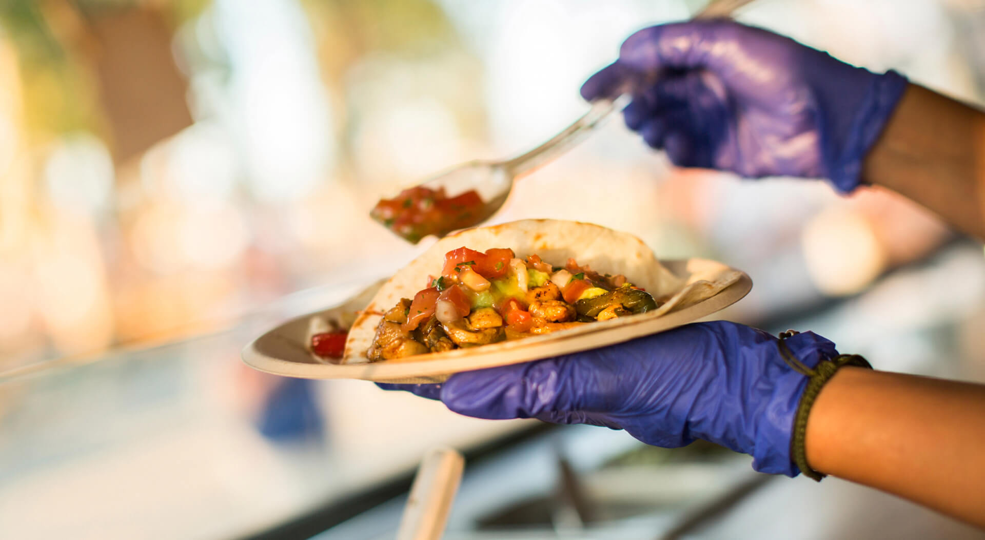 chef wearing gloves preparing tacos in a food truck