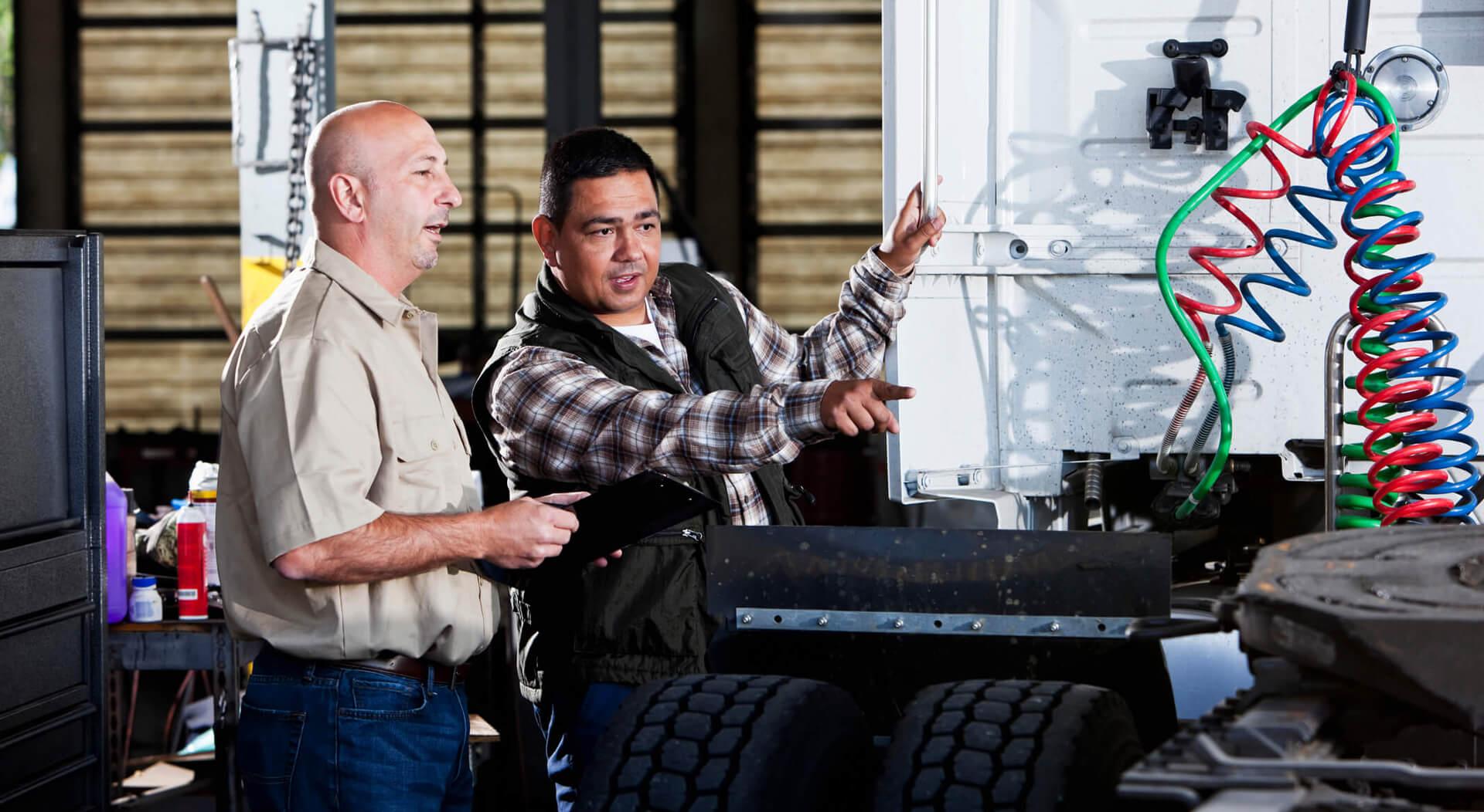 semi truck mechanics in a service garage with semi truck