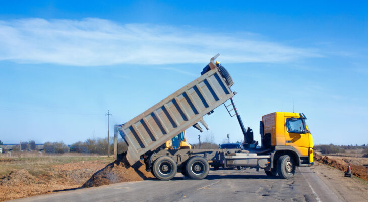 dump truck dumps sand on the side of the road during roadworks