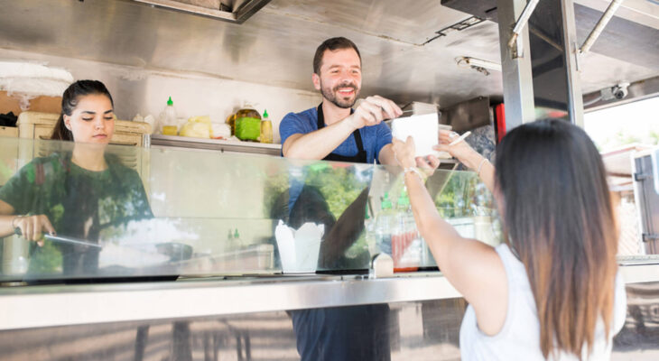 food truck server in a food truck handing over a box with oriental food to a female diner