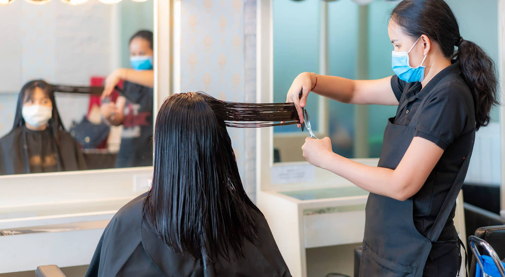 hairdresser trimming an asian woman's black hair with scissors in a mobile hair salon