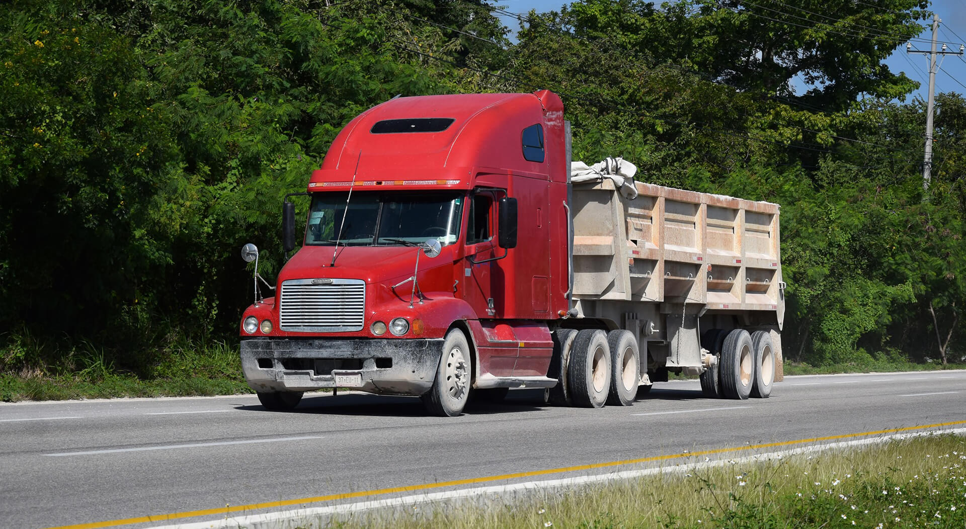red Freightliner truck driving on the road
