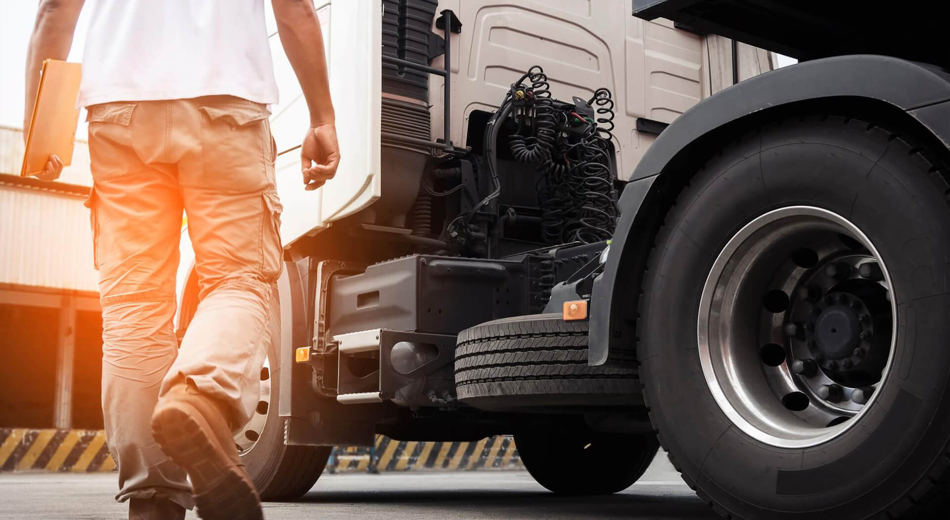 a truck driver walking around semi truck with big tires, inspecting and doing safety check