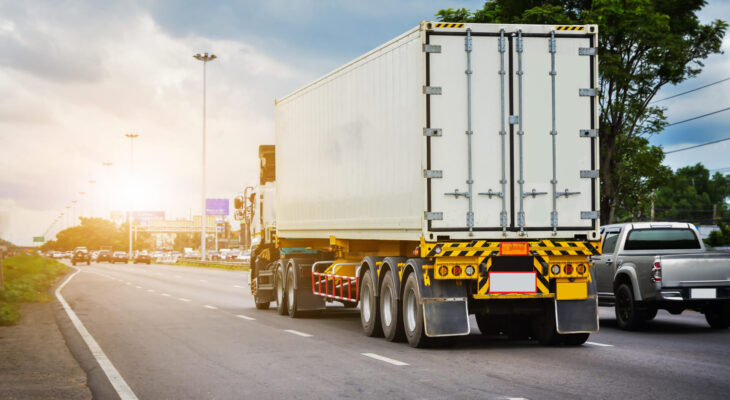 white semi truck driving on a road during summer