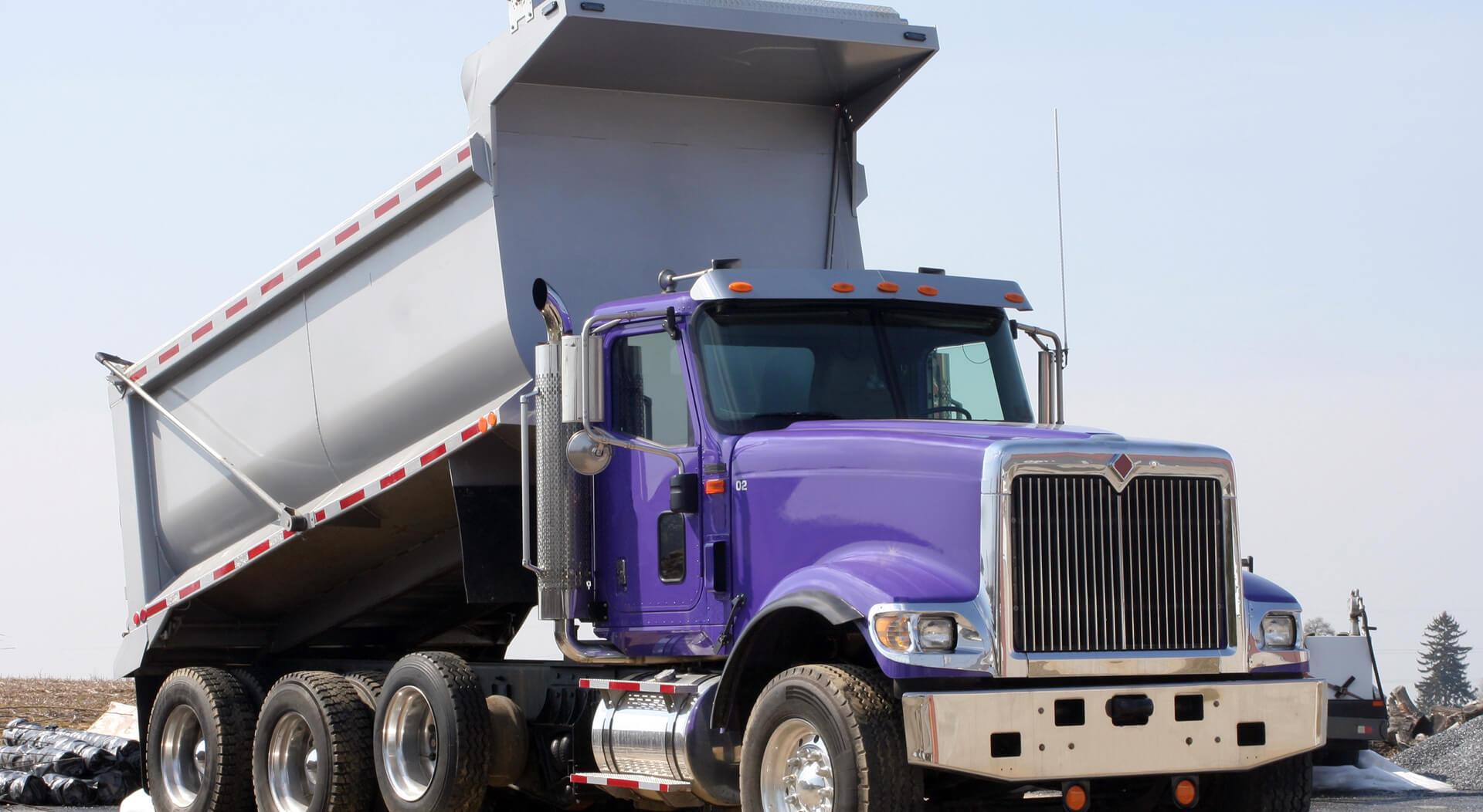 purple dump truck at a construction site