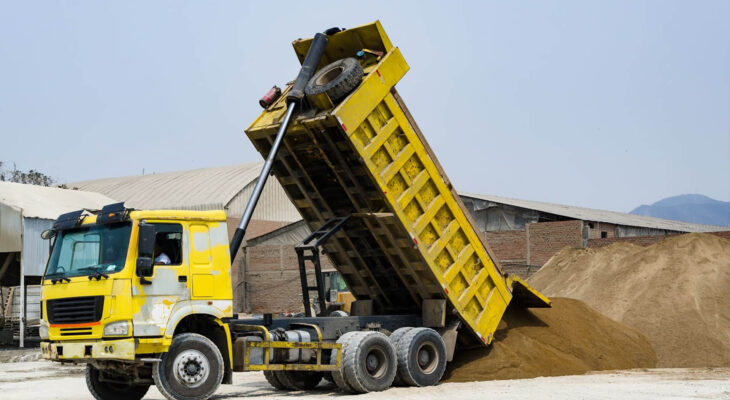 yellow dump truck delivering a load of dirt for a fill project at a new commercial development construction project