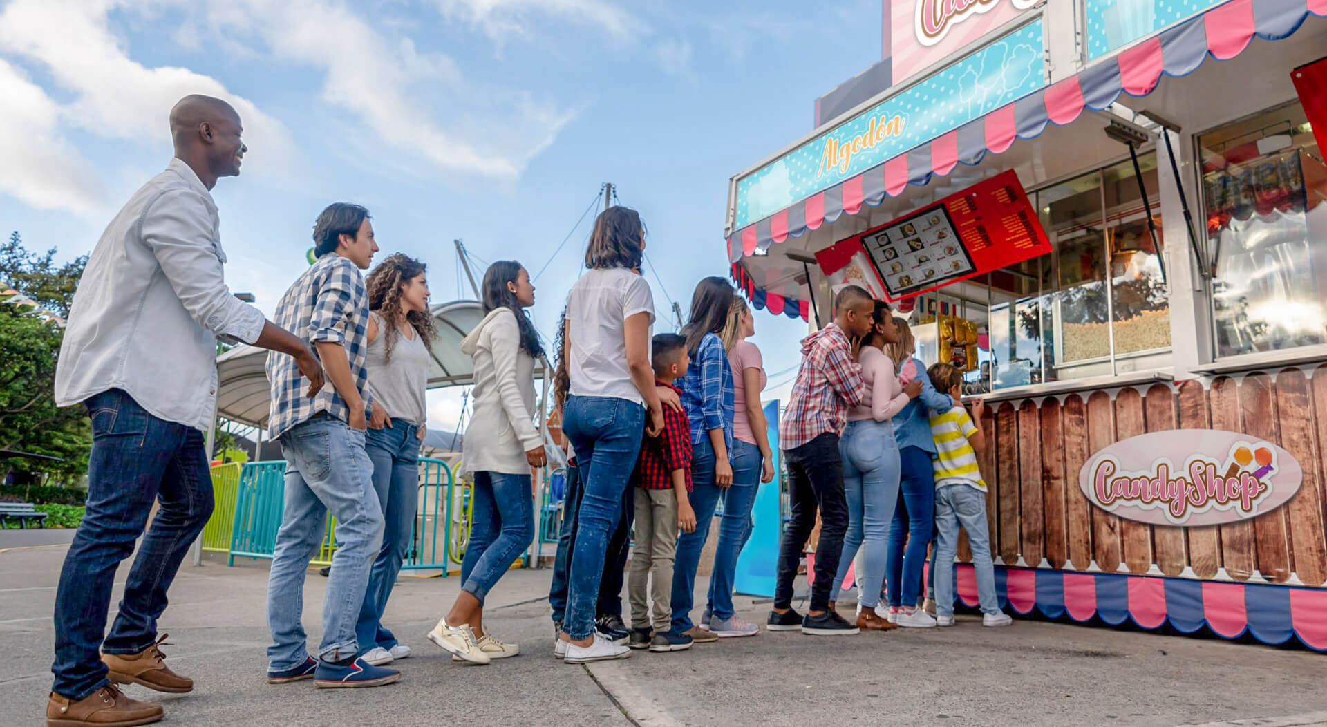 happy people at a funfair lined up to buy food at a candy shop