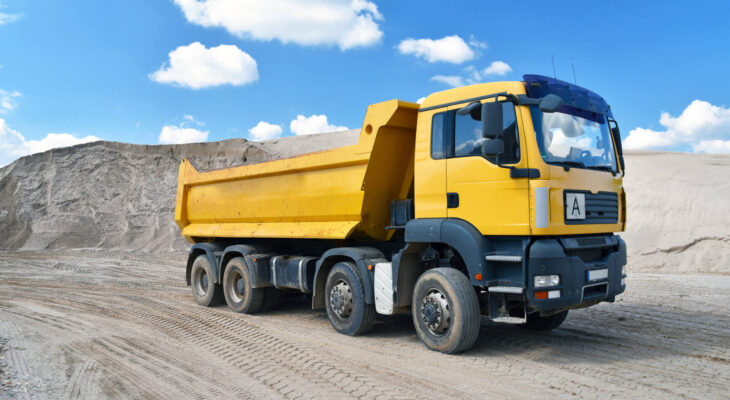 yellow dump truck transports sand in a gravel pit