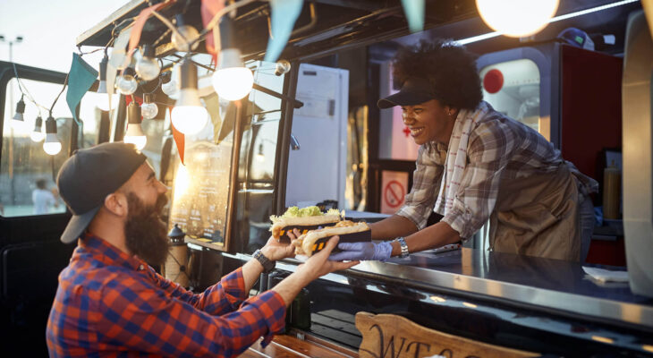 young man taking two sandwiches from polite female food truck employee