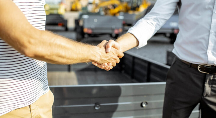 two businessmen shaking hands after sale of used semi truck