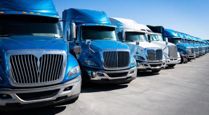 fleet of blue 18 wheeler semi trucks