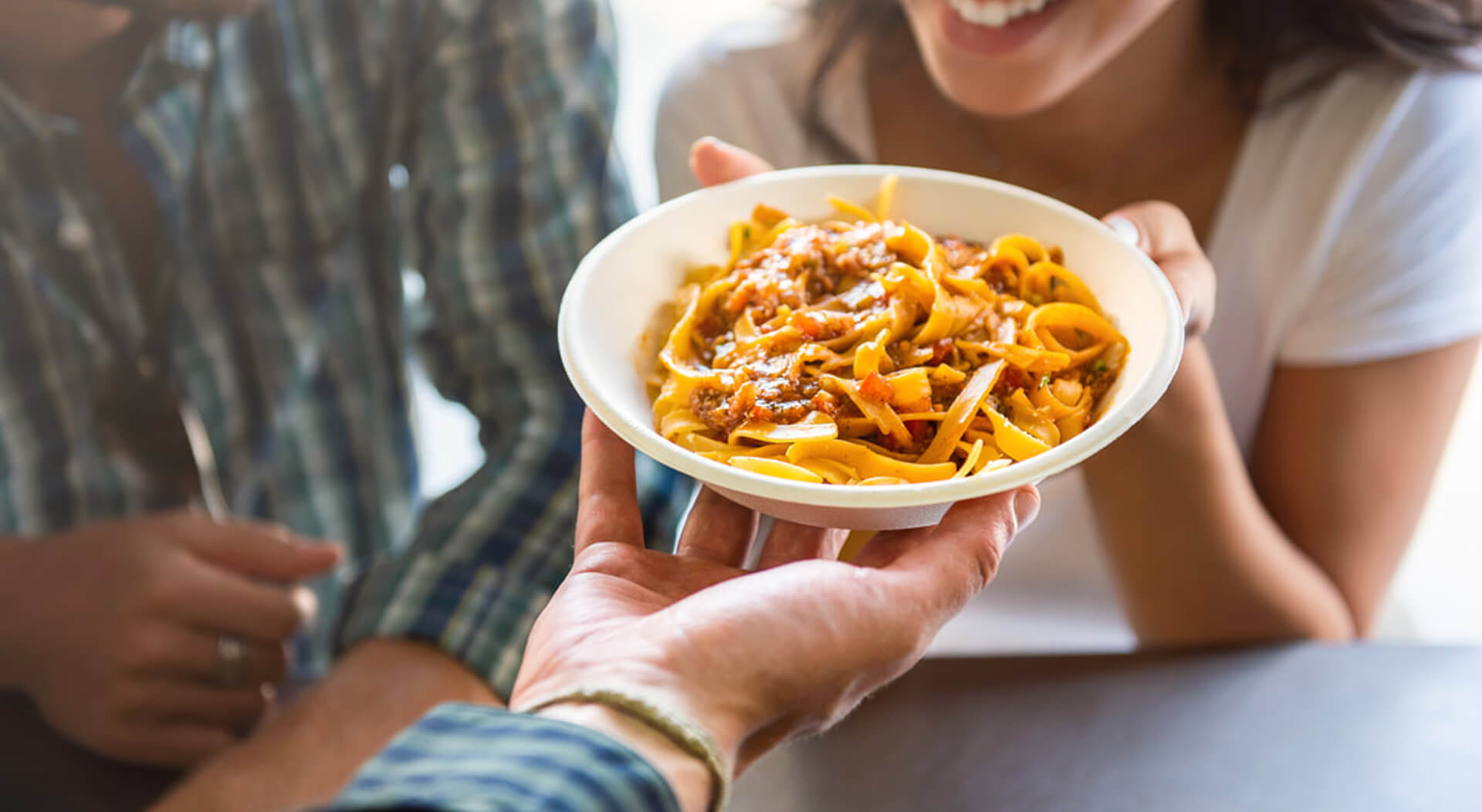 young woman smiling with pleasure while getting pasta that was just ordered at counter of food truck