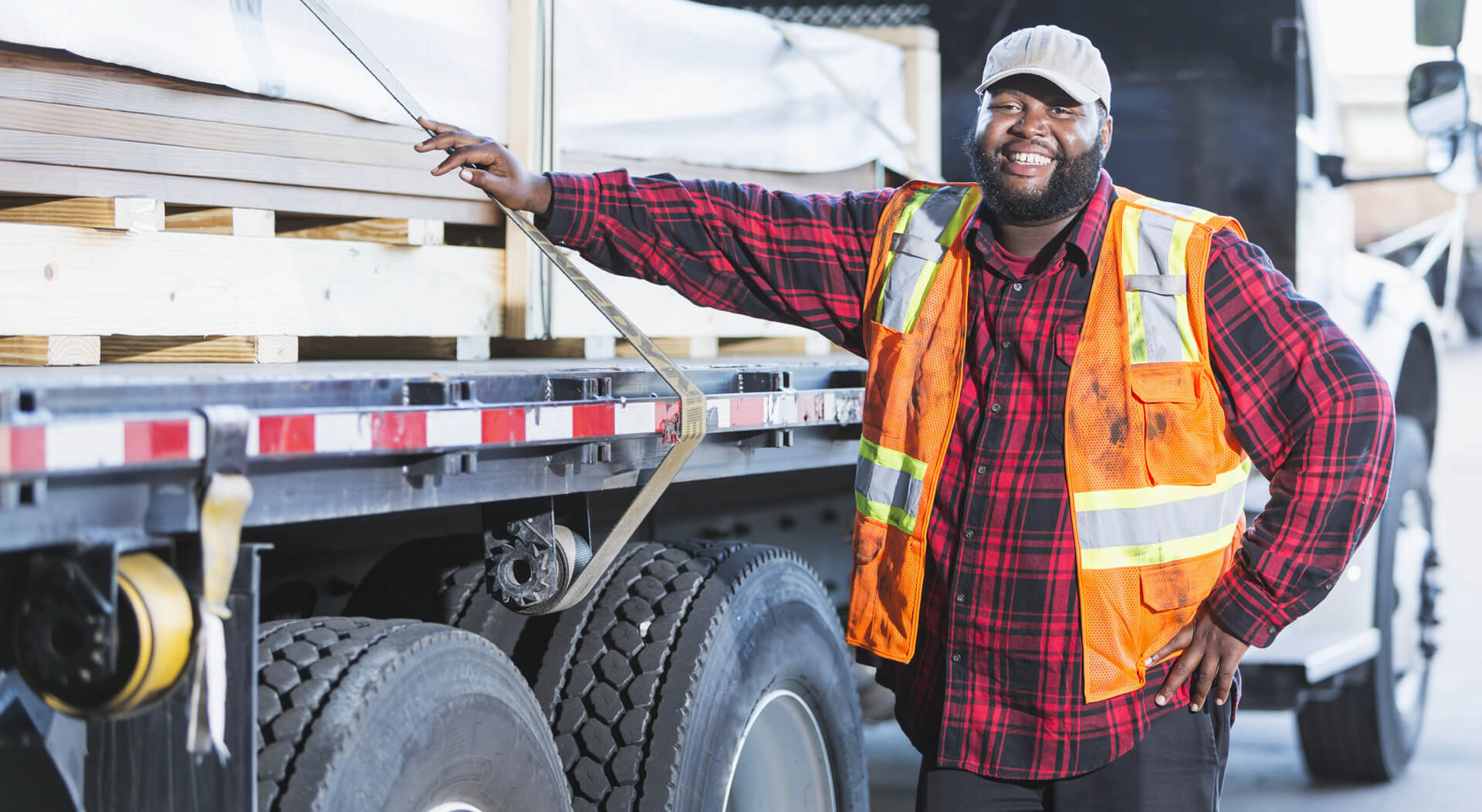 an African-American man in his 30s, standing next to a truck loaded with construction material. He is the truck driver delivering the supplies.
