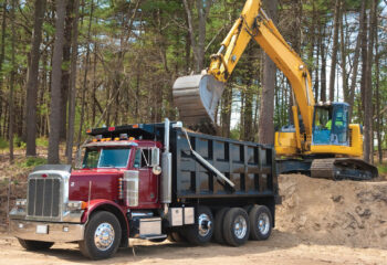 Excavator loading dumper truck with dirt at construction site