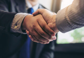 business men shaking hands during a meeting to sell truck