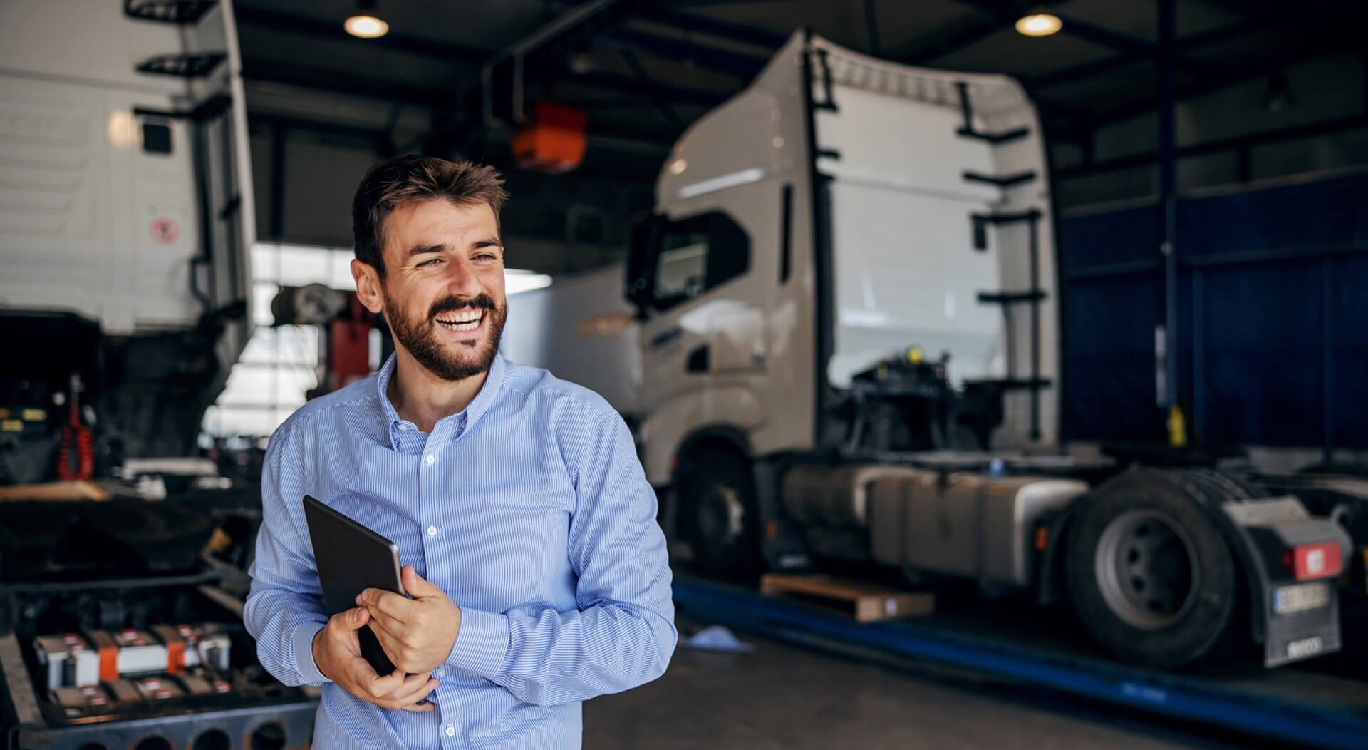 smiling truck owner standing in auto park and holding tablet