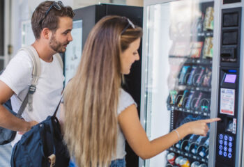 two university students taking something from vending machine