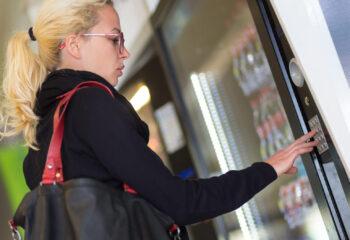 casual caucasian woman using a modern beverage vending machine